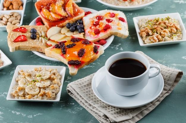 Овсянка в тарелках с фруктами, джемом, орехами, фруктовым сэндвичем, кофе