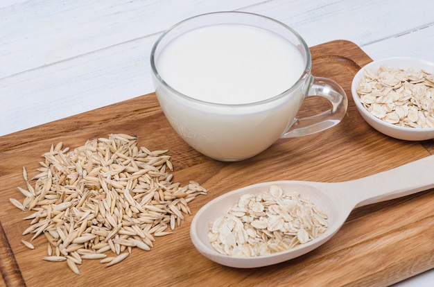 Oatmeal milk with oat seeds on wooden background