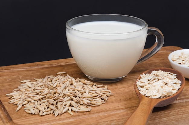 Oatmeal milk with oat seeds on wooden table