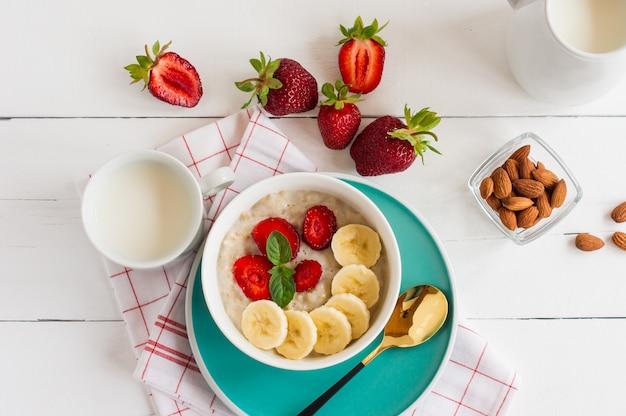 Овсяные хлопья мюсли в миске с клубникой, бананом и миндалем. здоровый завтрак.
