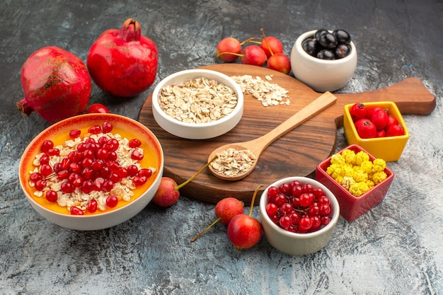 Oatmeal oatmeal on the board two pomegranates red currants cherries grapes