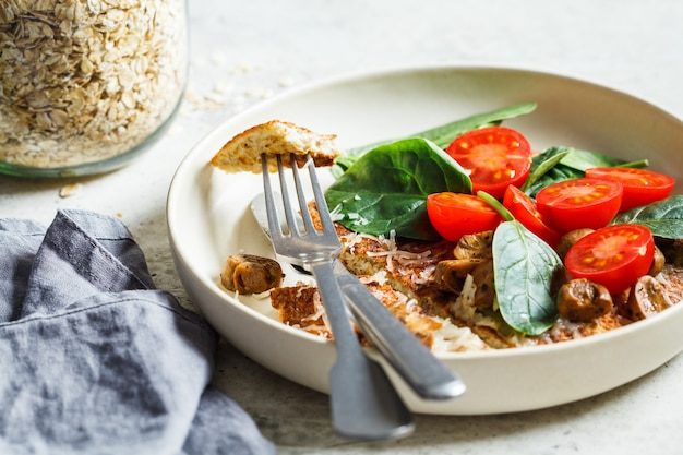Блинчик из овсяного омлета с сыром, грибами, помидорами и шпинатом. здоровый фитнес-завтрак.