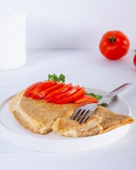 녹은 치즈와 흰색 나무 테이블에 빨간 토마토 오트밀 팬케이크