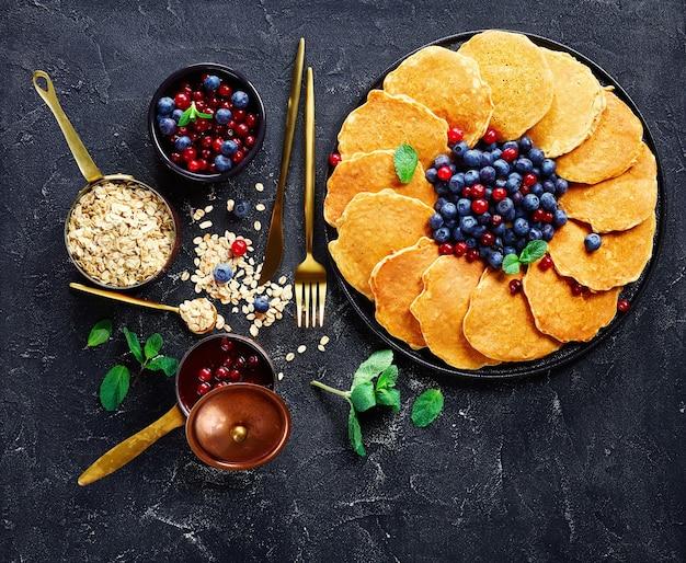 Овсяные оладьи со свежей черникой и клюквой на черном блюде, ингредиенты, золотая вилка и нож, клюквенный соус