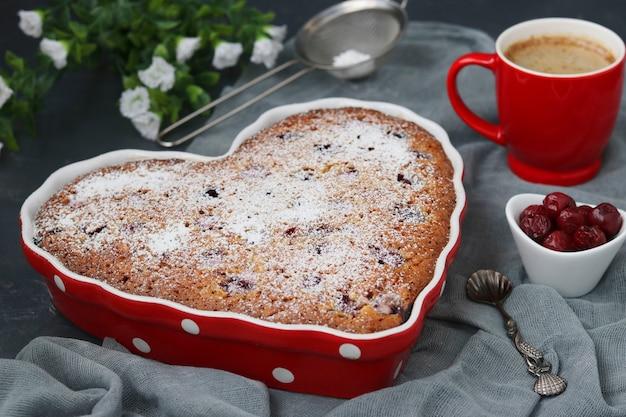 Пирог овсяный с вишней посыпанный сахарной пудрой в керамической форме в форме сердца на темном