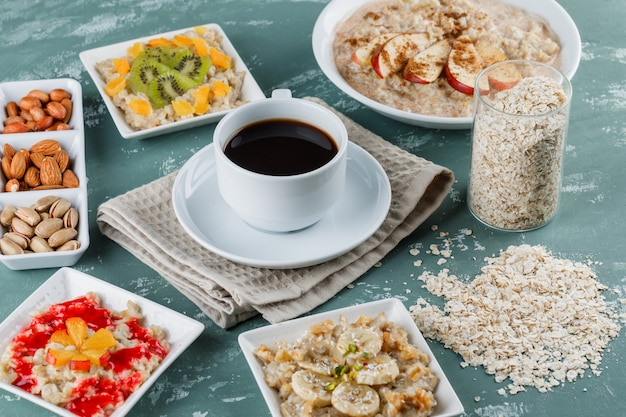 Oatmeal in plates with fruits, jam, nuts, cinnamon, coffee, oat flakes