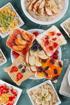 Oatmeal in plates with fruits, jam, nuts, cinnamon, fruit