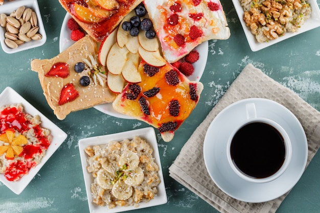 Oatmeal in plates with fruits, jam, nuts, fruit sandwich, coffee