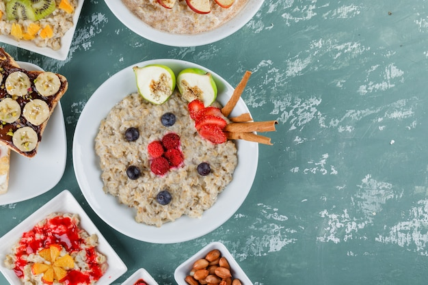 Oatmeal in plates with fruits, jam, sandwich, cinnamon, nuts