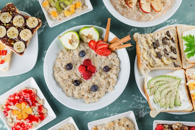 Oatmeal in plates with fruits, jam, sandwich, cinnamon