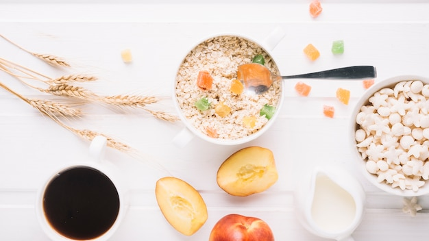 Oatmeal porridge in bowl with cereals and peach on table