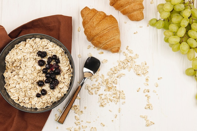 Oatmeal porridge bowl with grapes and croissants