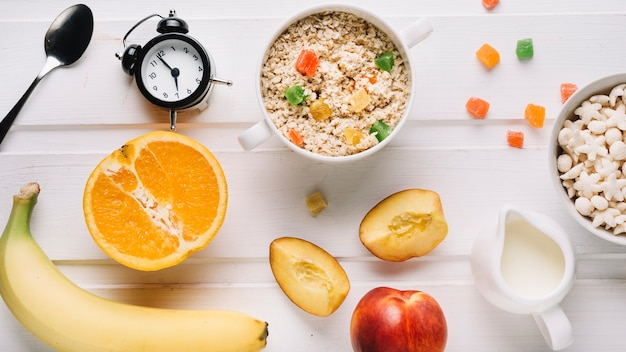 Oatmeal porridge, fruits, cereals and milk with alarm clock on white table