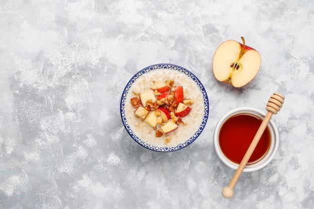 Овсяная каша в миске с медом и кусочками красного яблока, вид сверху