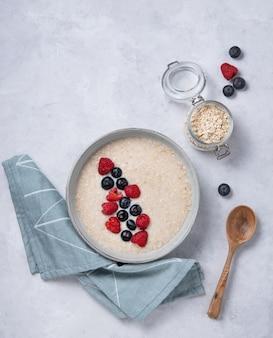 Овсяная каша в серой миске с черникой и малиной. здоровый завтрак, диета и энергетическая еда. вид сверху и копировать пространство