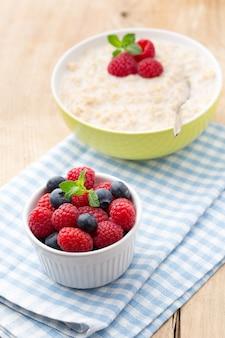 Овсяная каша в миске с ягодами малины и ежевики.
