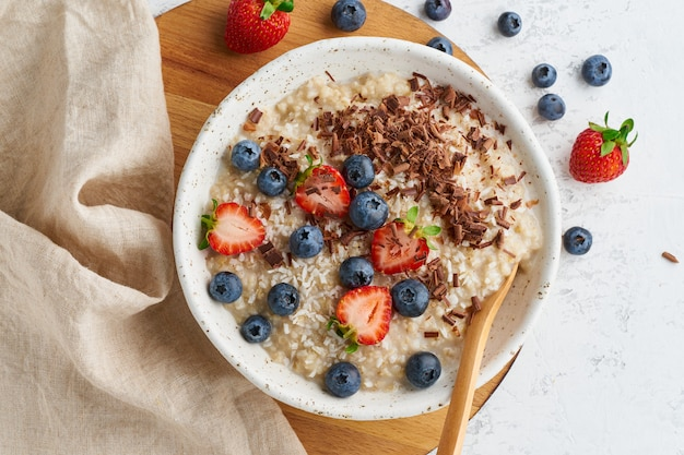 Oatmeal porridge rustic with berries and chocolate
