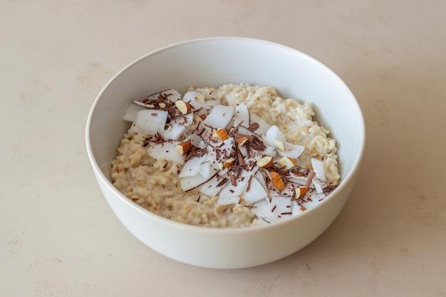 アーモンド、ココナッツ、チョコレートが入ったオートミールのお粥。健康的な食事。ベジタリアンフード。朝ごはん。ダイエット。