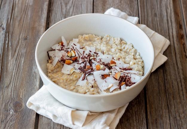 아몬드, 코코넛, 초콜릿이 들어간 오트밀 죽. 건강한 식생활. 채식주의 자 음식. 아침밥. 다이어트.