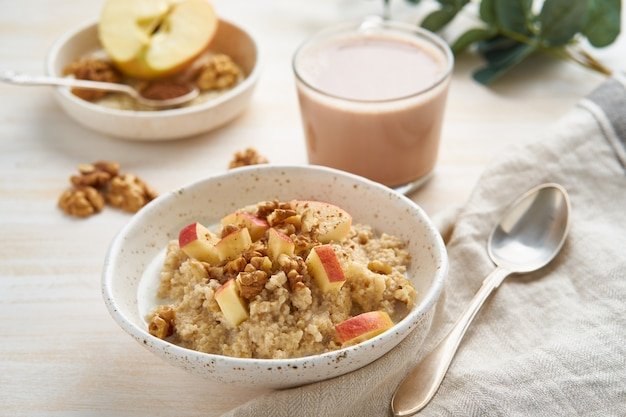Oatmeal porridge with apple, walnuts and cup of cocoa on white wooden light