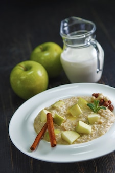 Oatmeal porridge with apples and cinnamon on a black wooden table.
