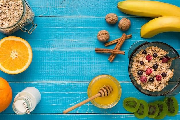 소박한 나무 배경에서 건강한 아침 식사를 위해 계란과 함께 그릇에 바나나, 키위 과일, 견과류, 꿀을 넣은 오트밀 죽. 아침 식사를 위한 건강식. 평면도. 복사 공간