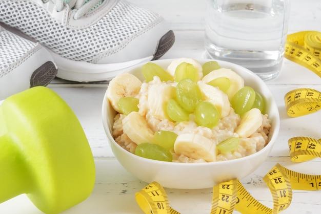 Овсяная каша с кусочками банана и виноградом, стакан воды, желтые гантели, кроссовки, измерительная лента на белой деревянной поверхности крупным планом