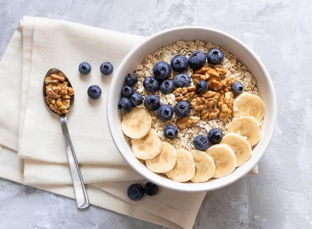 オートミール。健康的な朝食やランチにバナナ、ブルーベリー、クルミの粥。