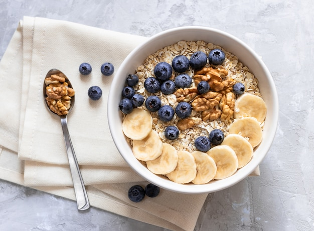 Oatmeal. porridge with bananas, blueberries and walnut for healthy breakfast or lunch.