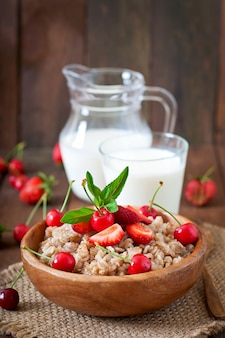 Oatmeal porridge with berries in a white bowl