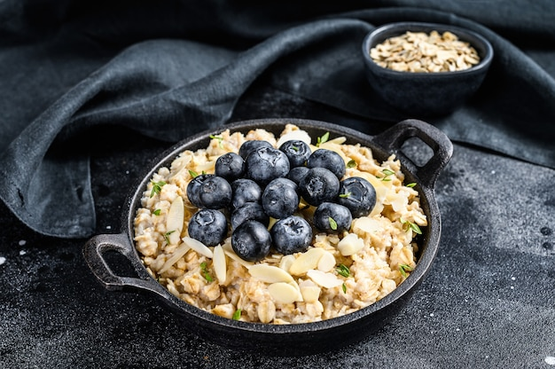 Oatmeal porridge with blueberries and almonds. black background. top view.