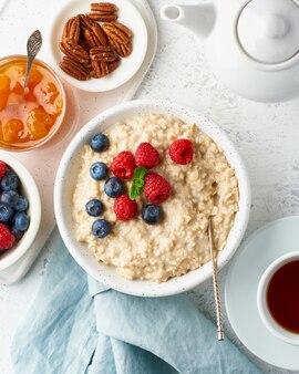 Овсяная каша с черникой, малиной, вареньем, вертикаль, вид сверху. завтрак с ягодами