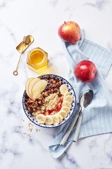 Овсяная каша с карамелизированными яблоками с корицей, бананом, тертой клубникой и медом на светлом фоне мрамора, вид сверху.