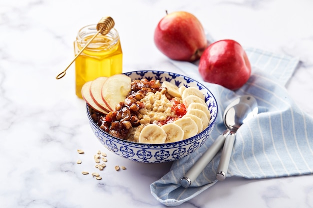 Oatmeal porridge with caramelized apples with cinnamon, banana, grated strawberries and honey on light marble background