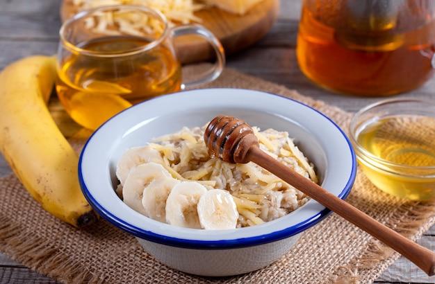 木製の背景の白いプレートにチーズとバナナとオートミールのお粥。朝ごはん