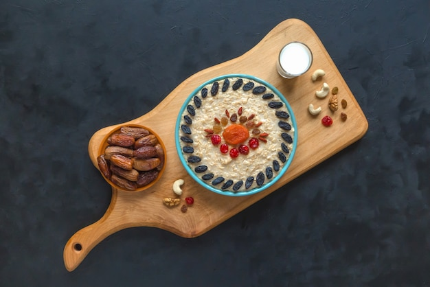 Oatmeal porridge with dried fruits on a black table. top view.