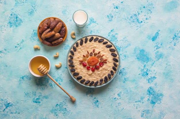 Oatmeal porridge with dried fruits on a blue table. top view.