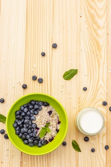 Oatmeal porridge with fresh blueberry, mint leaves and yogurt