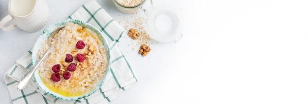 가벼운 돌이나 콘크리트 배경의 세라믹 접시에 신선한 라즈베리, 호두, 버터를 넣은 오트밀 죽. 선택적 초점