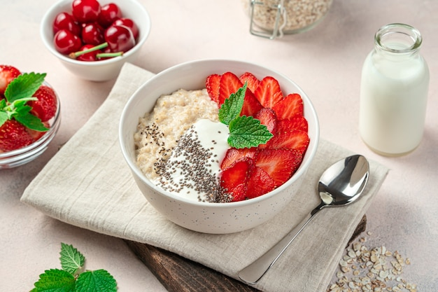 Oatmeal porridge with fresh strawberries on a light pink background