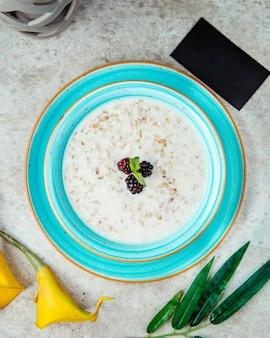 Oatmeal porridge with milk and raspberries top view