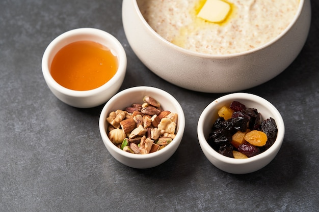 Oatmeal porridge with raisins, honey and nuts in a bowl