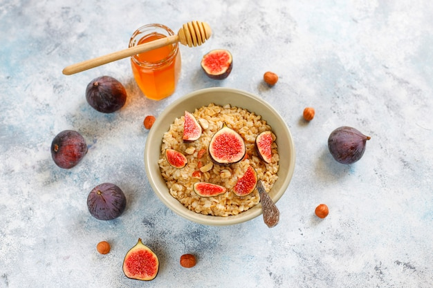Oatmeal porridge with red figs and walnuts, honey in a bowl