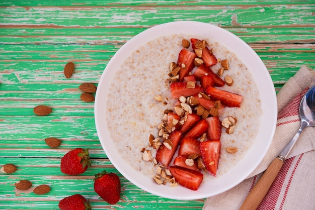 Oatmeal porridge with strawberries and almonds in a white plate on a rustic background, copyspace, top view