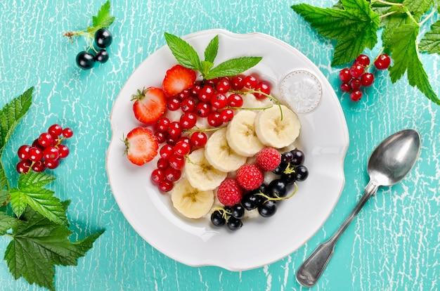 Каша овсяная с клубникой, бананом, малиной, черной и красной смородиной на завтрак