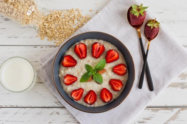 Oatmeal porridge with strawberries in dark bowl. healthy breakfast with oatmeal and fresh organic berries, top view.
