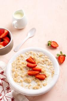 분홍색 배경에 리넨 냅킨에 흰색 접시에 딸기와 오트밀 죽. 아침 식사 건강 식품 개념입니다. 평면도