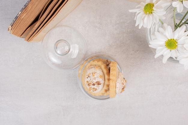 유리 항아리, 책 및 데이지에 오트밀 건포도 쿠키.