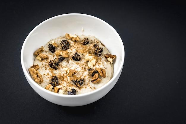 Oatmeal recipe with walnuts, prunes, cinnamon and sugar on black