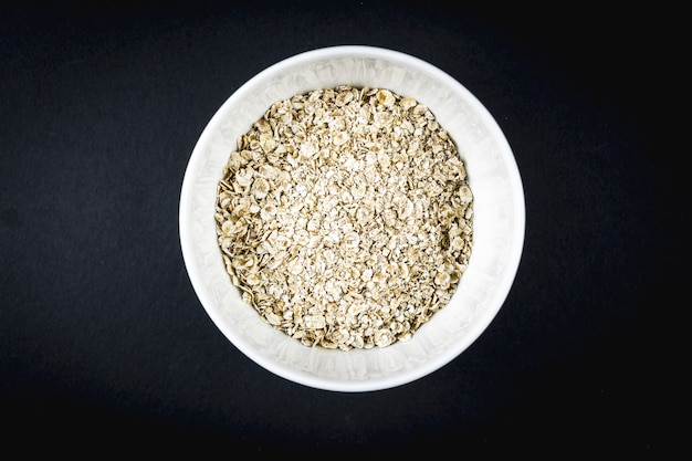 Oatmeal recipe with walnuts, prunes, cinnamon and sugar. oatmeal in a white cup